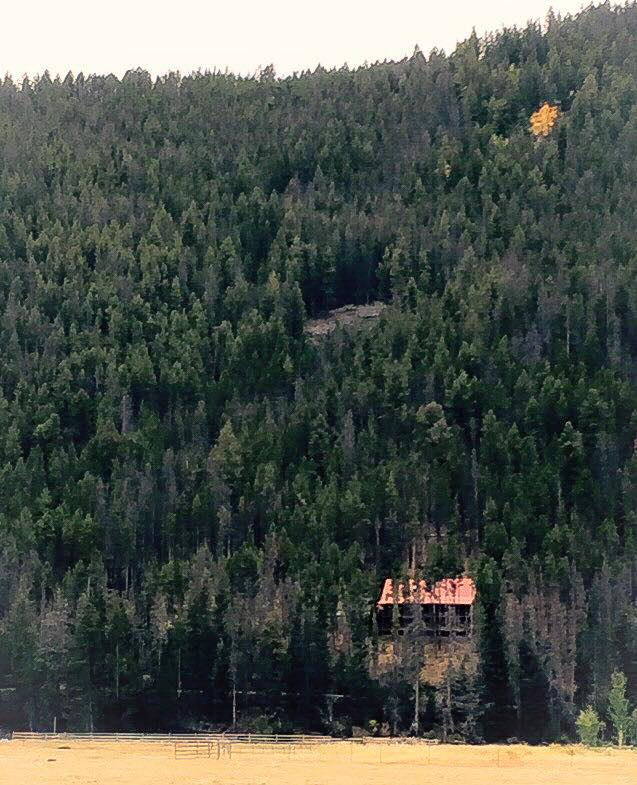 The mountainside log home with a spot of gold above